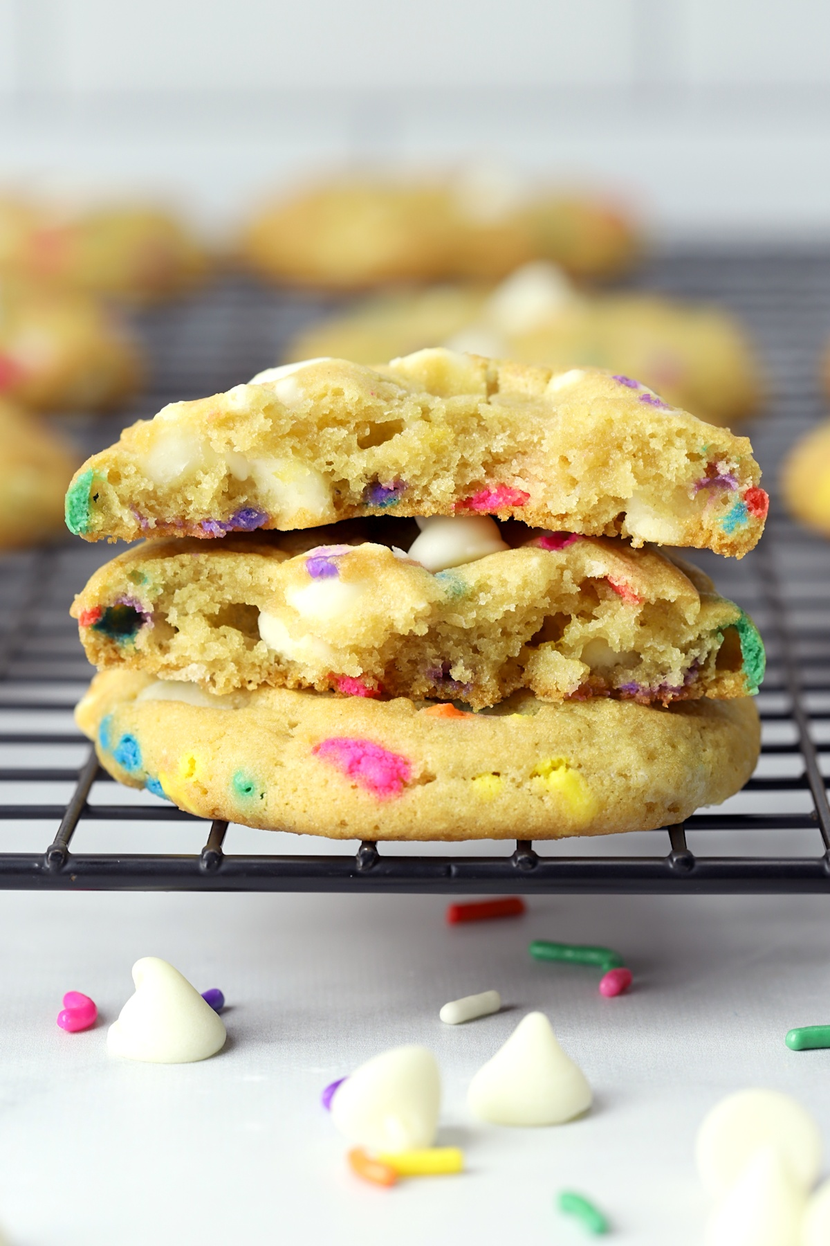 Cookie broken in half to show soft center with white chocolate chips and sprinkles.