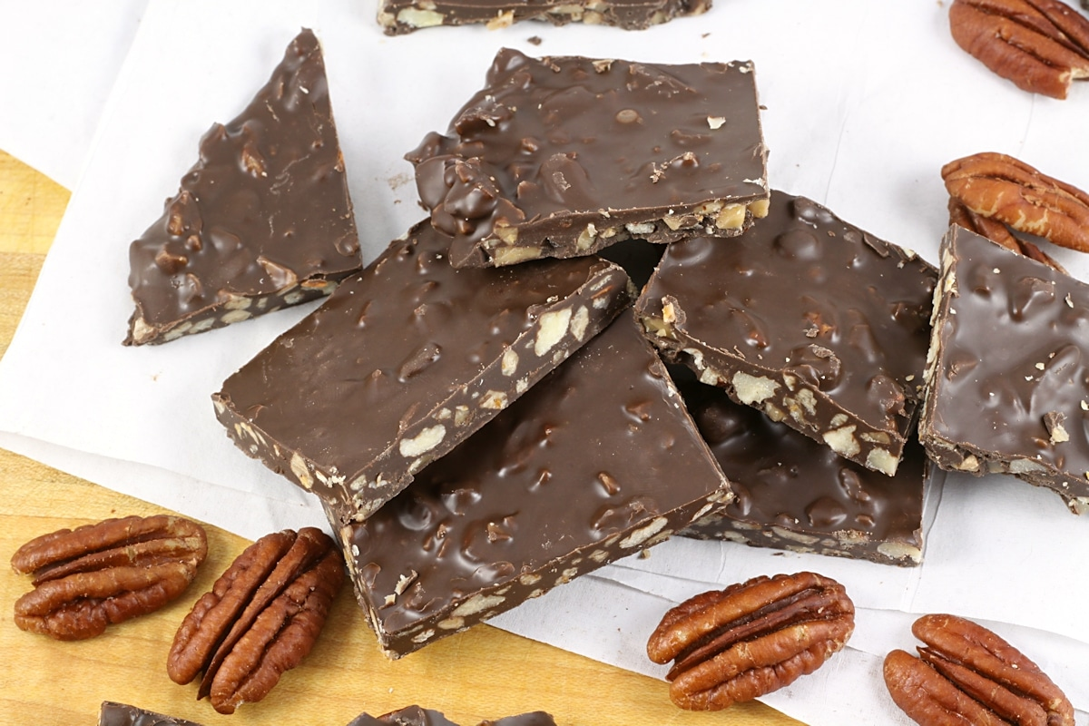 Chocolate candy filled with pecans and toffee on a wooden cutting board.