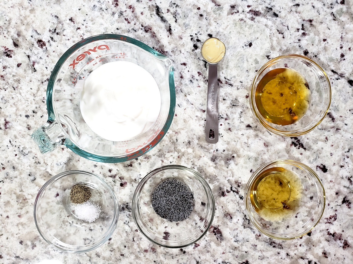 Ingredients to make greek yogurt poppy seed dressing on a counter top.