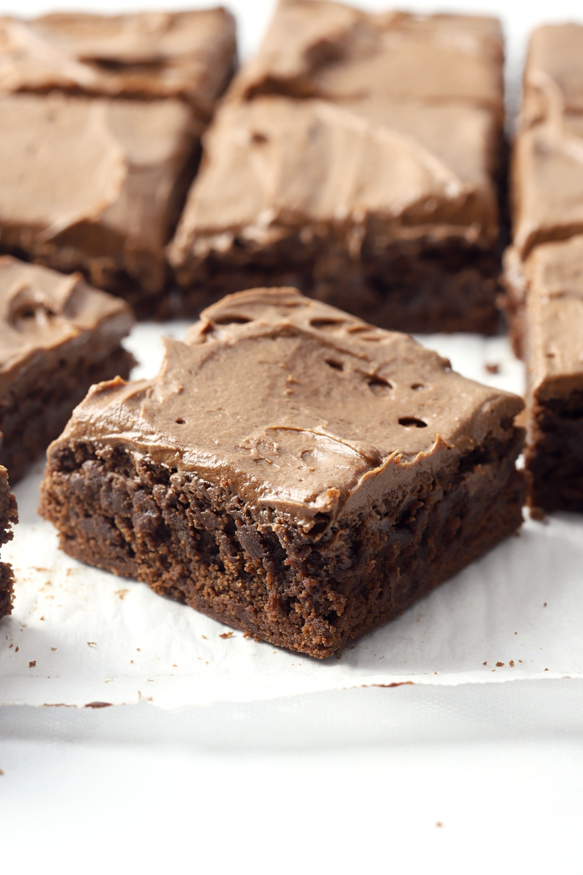 Chocolate frosted brownies on a piece of parchment paper.