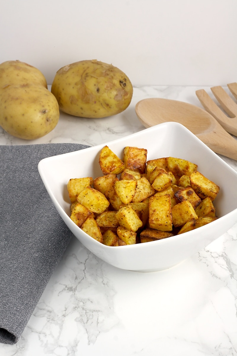 Roasted potatoes in a white bowl.