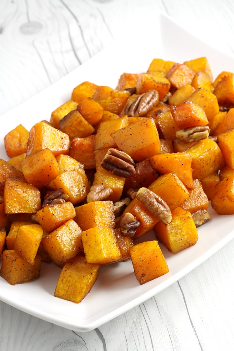 A white serving dish filled with cubed butternut squash and pecans.