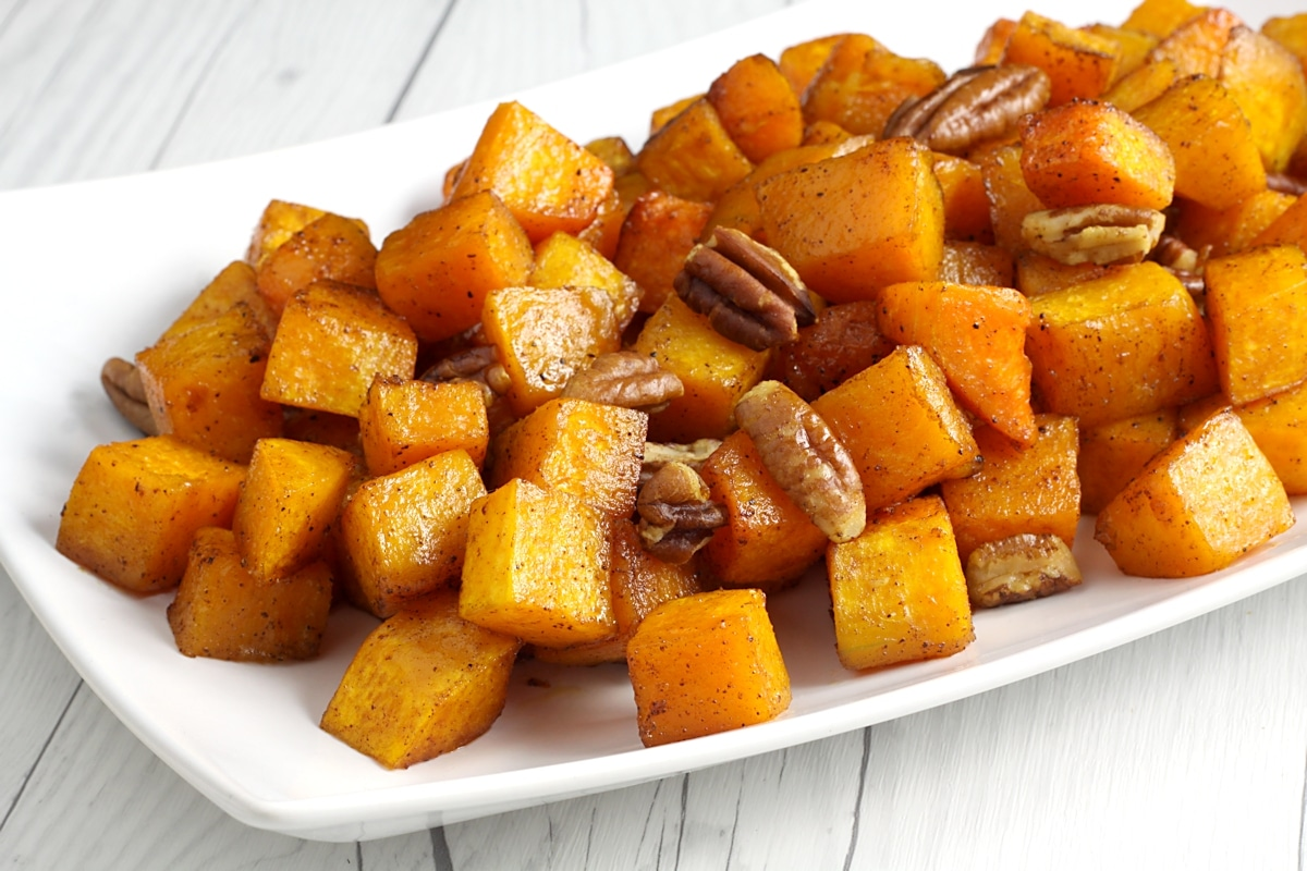 Roasted butternut squash and pecans on a serving plate.