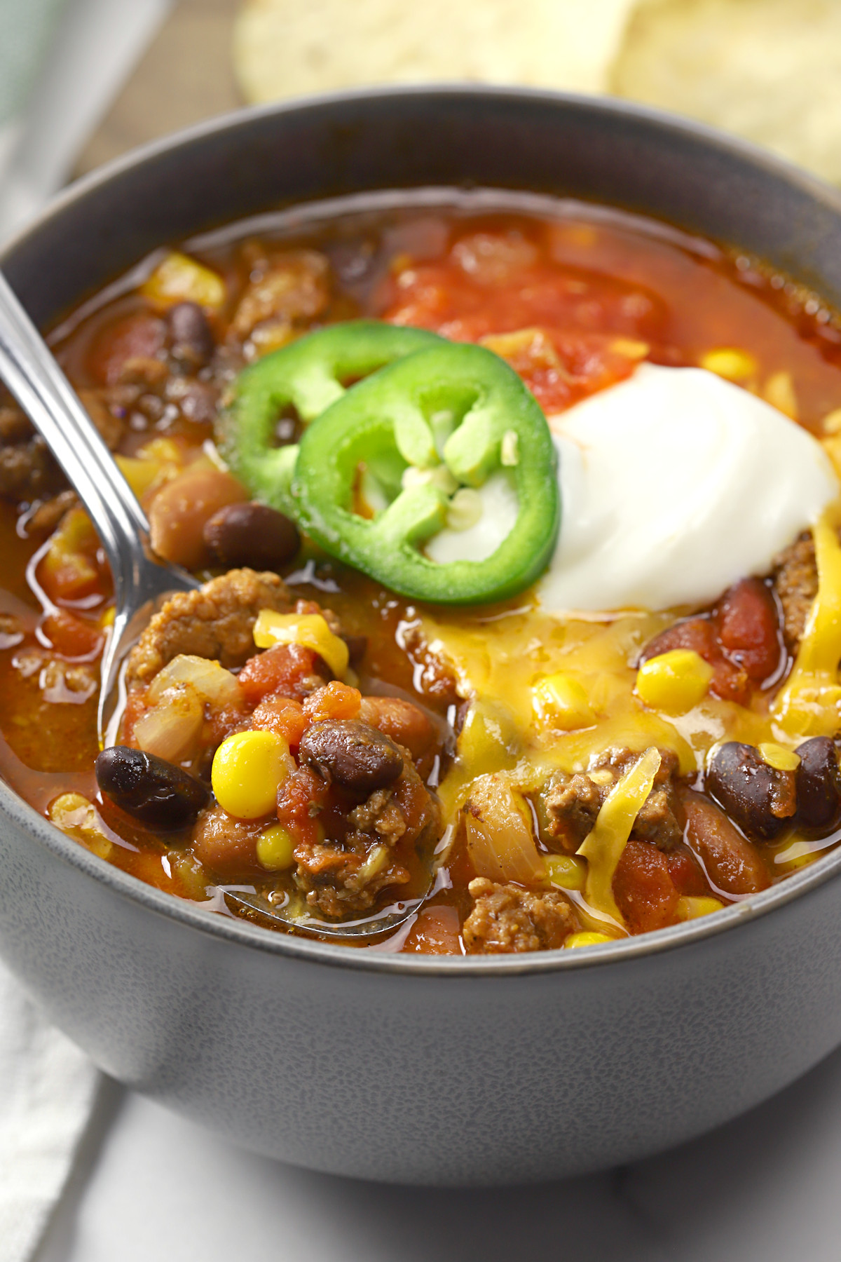 Metal spoon in a bowl of chili.