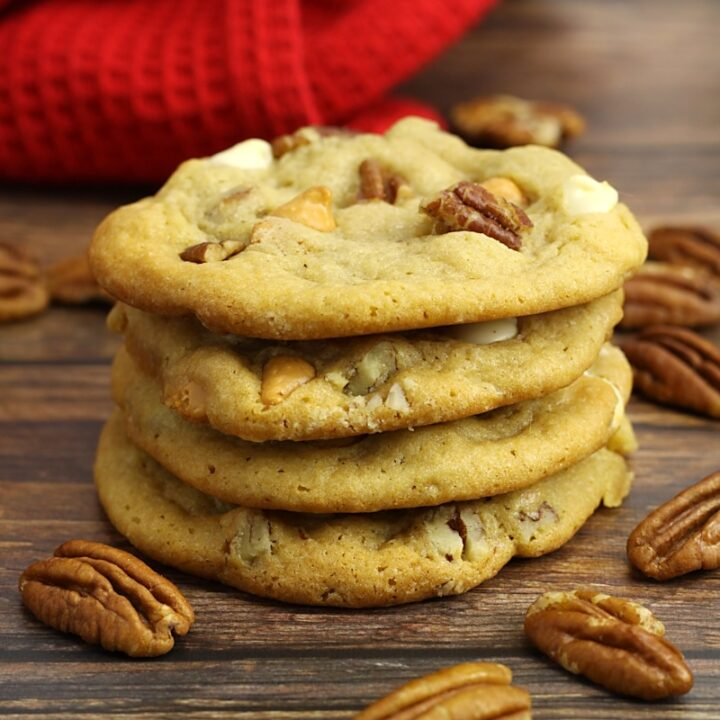 A stack of butter pecan cookies with pecans scattered on a counter top.