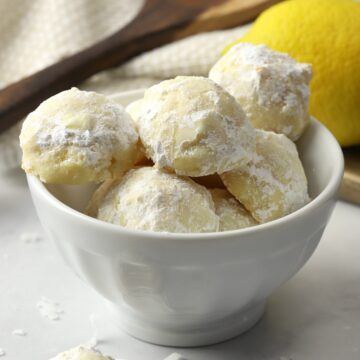 A white bowl filled with snowball cookies.