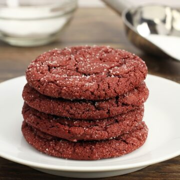 A stack of red cookies on a white plate.