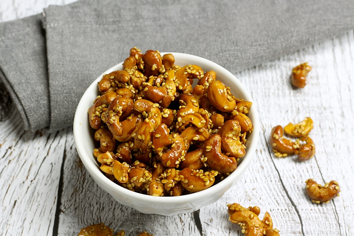 honey roasted cashews with sesame seeds in a decorative bowl.