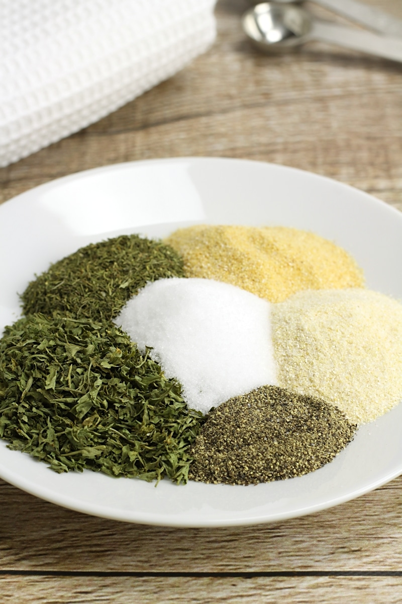 A white plate with parsley, dill, and other spices.