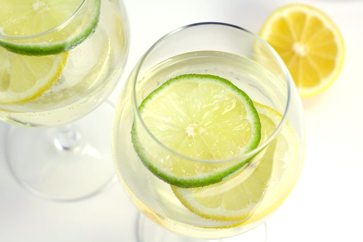 Lime and lemon wedges floating in a glass of wine.