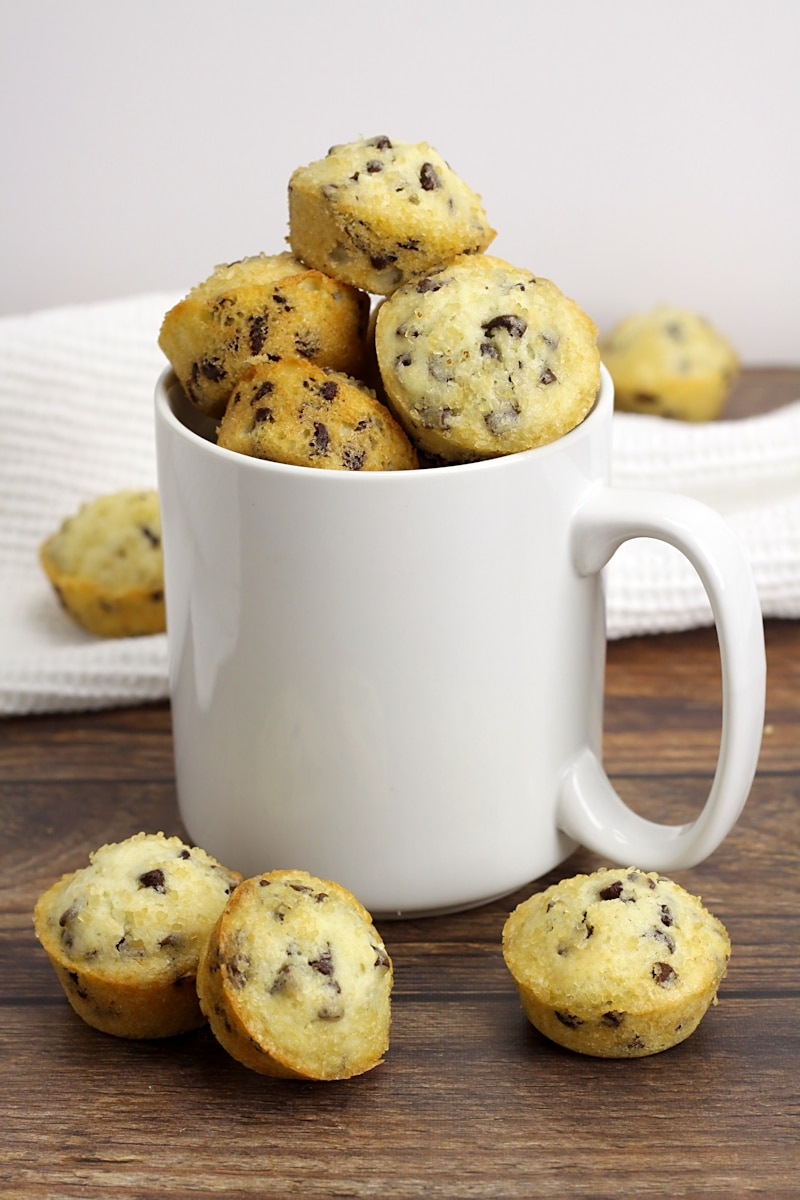 A white coffee mug filled with mini muffins.