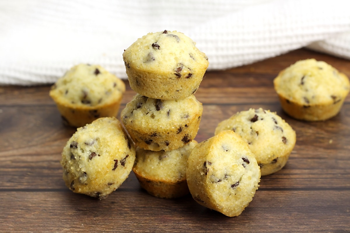 Chocolate chip mini muffins stacked on a wood counter top.