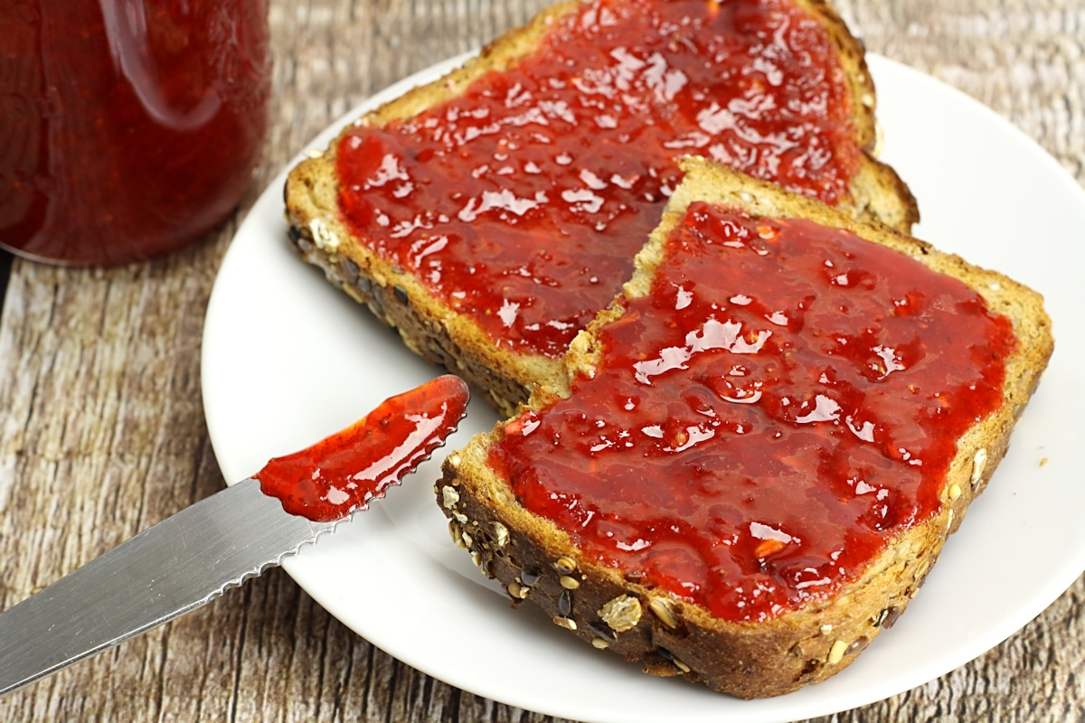 Two slices of toast with strawberry jam on top.