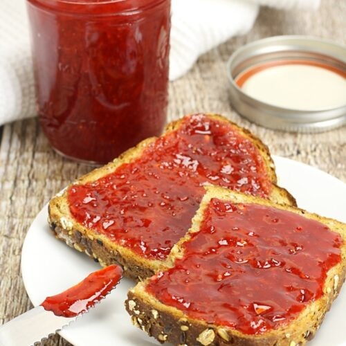 Toast on a white plate with strawberry jam.