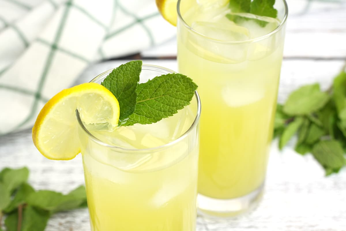 A lemon slice and mint leaf on top of a glass of lemonade.