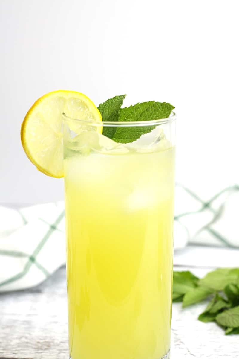 A tall glass of lemonade with a mint sprig.