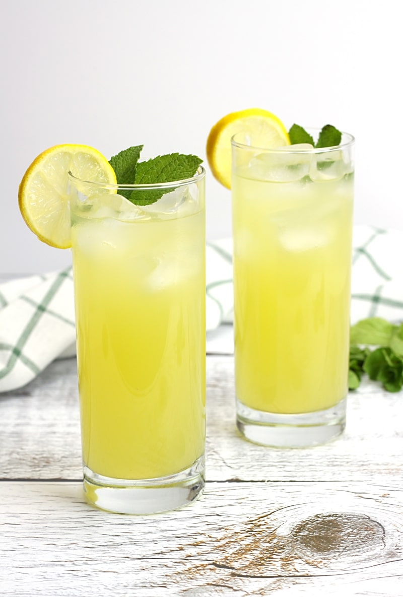 Two glasses of lemonade on a white wood counter top.