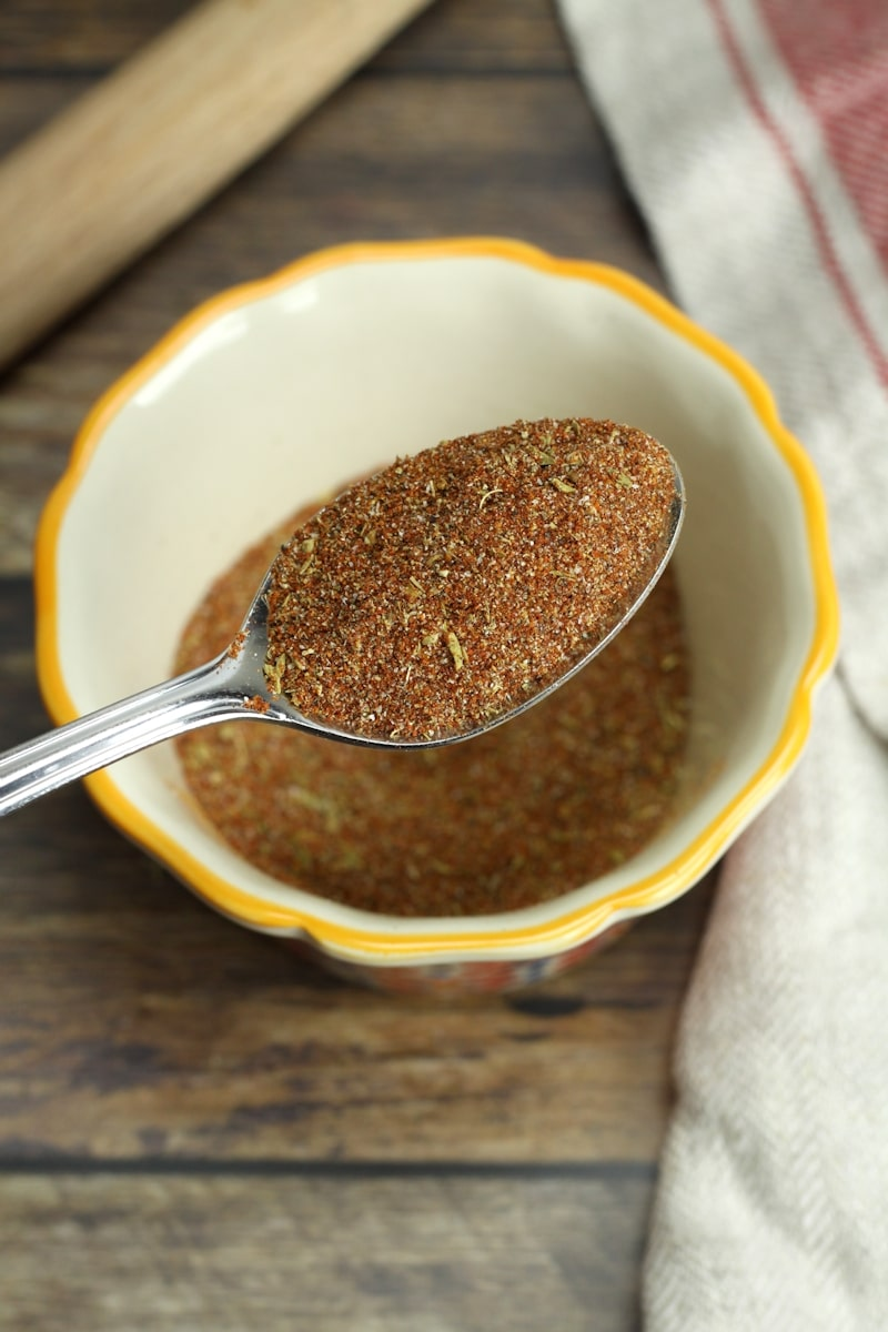 A metal spoon scooping cajun seasoning from a bowl.