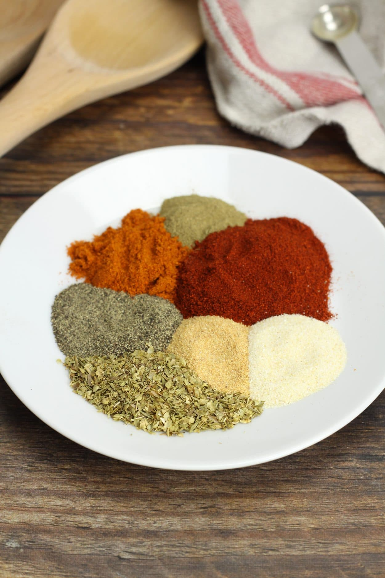 A white plate with a variety of spices and herbs.