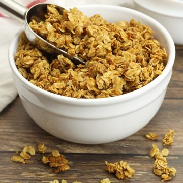 A white bowl filled with granola, with a metal scoop.