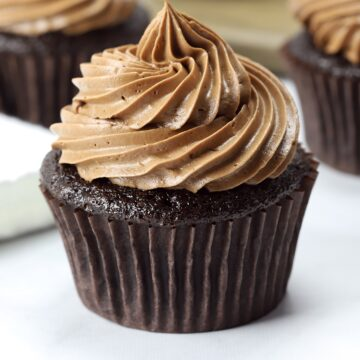 A chocolate cupcake topped with piped chocolate frosting.
