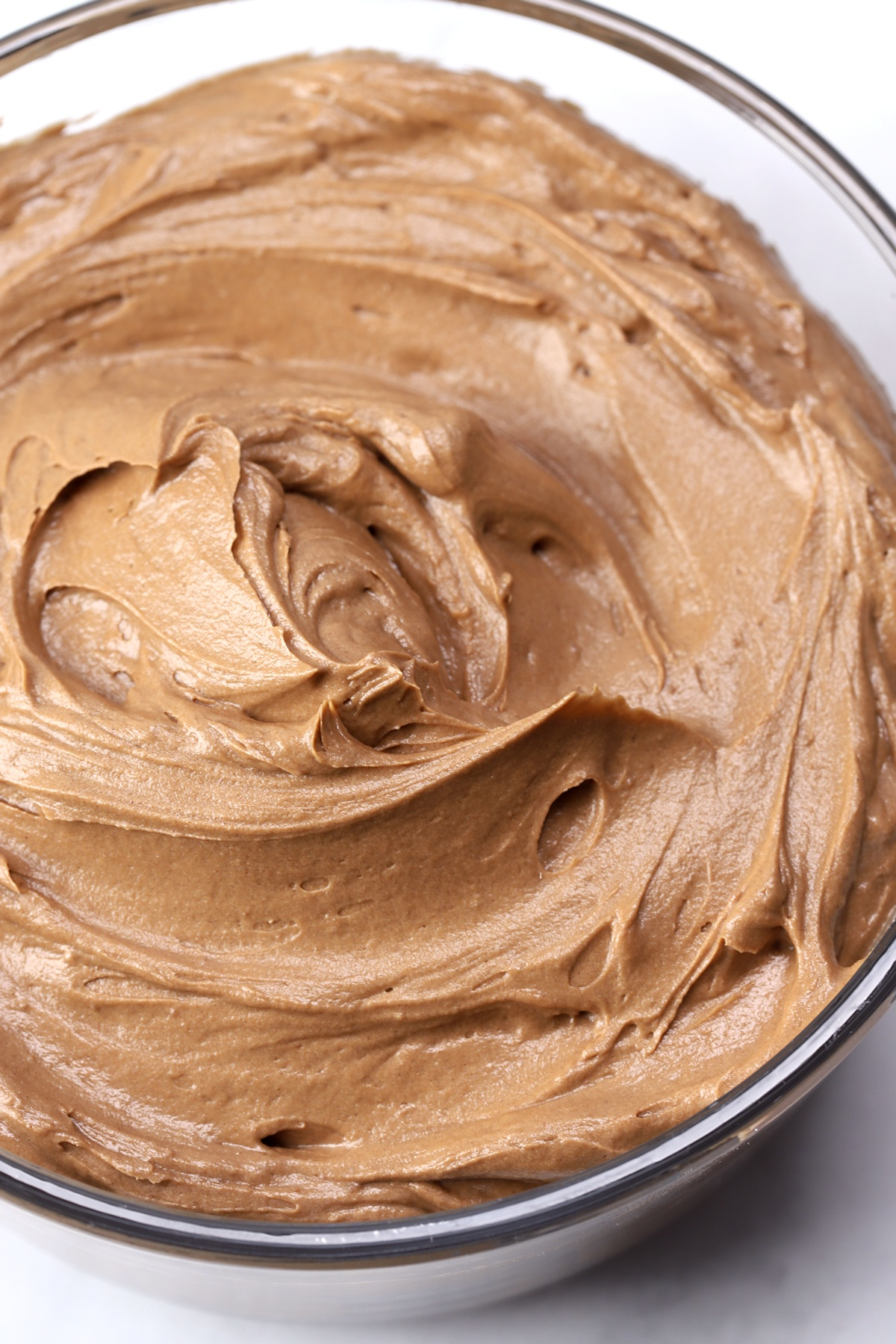 Chocolate buttercream frosting in a glass bowl.