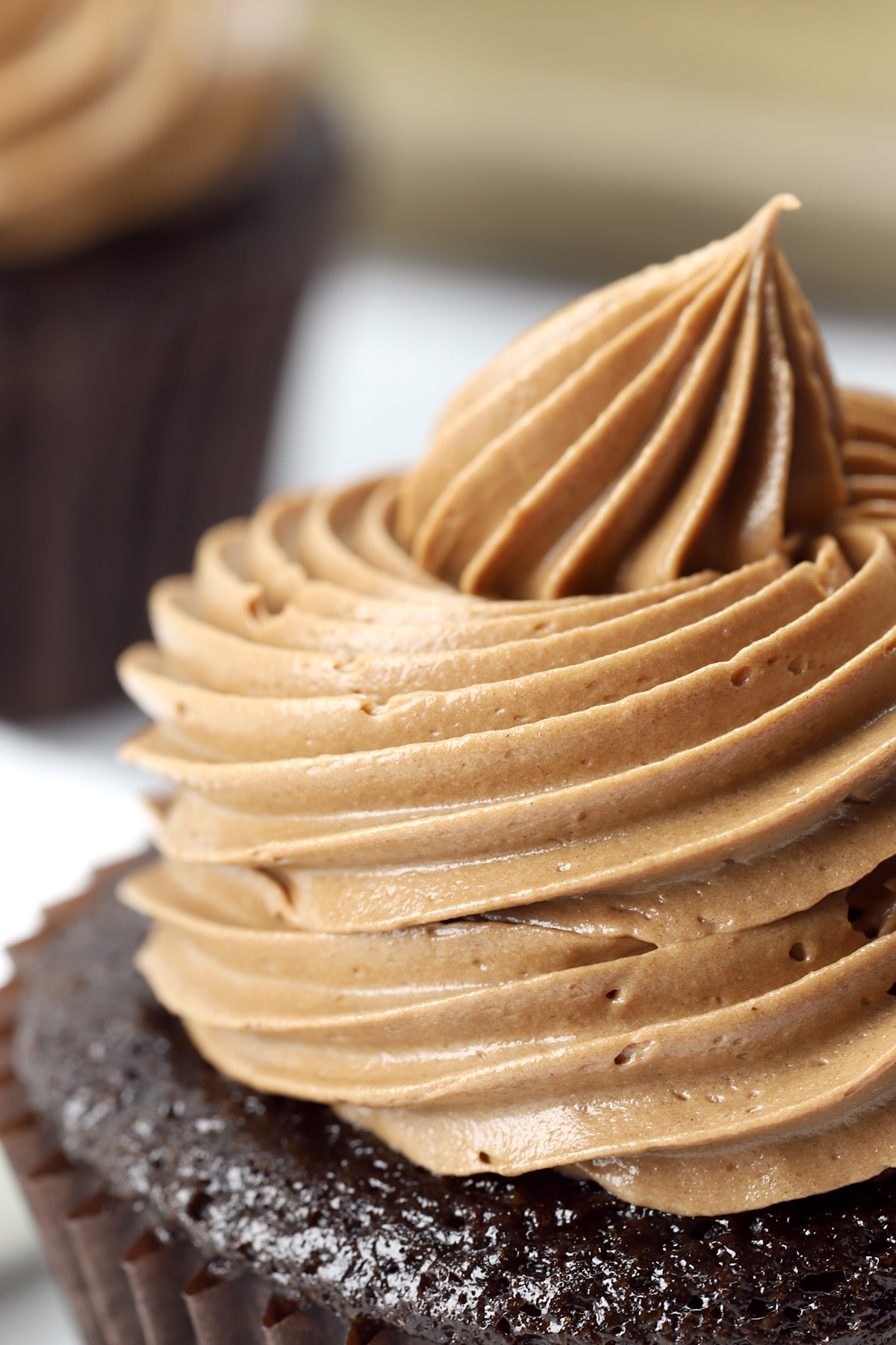 Chocolate frosting piped onto a cupcake.