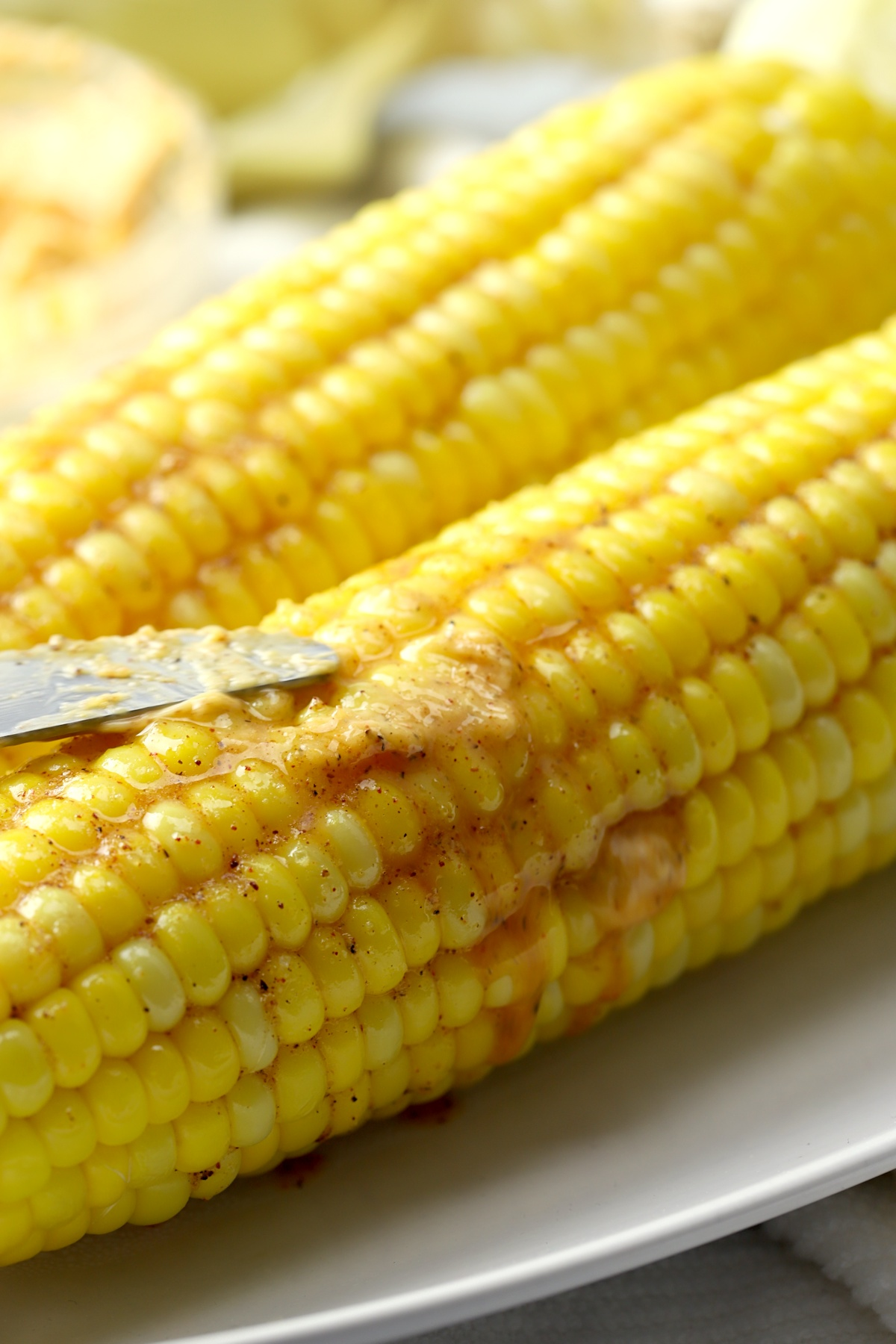 Spreading butter on an ear of corn.