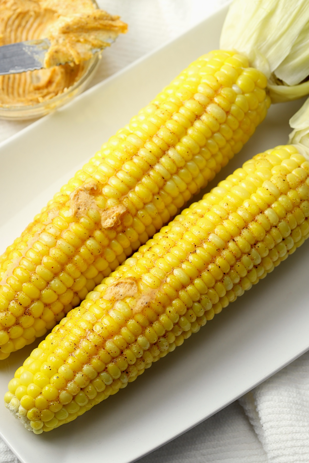 Two corn cobs on a white plate.