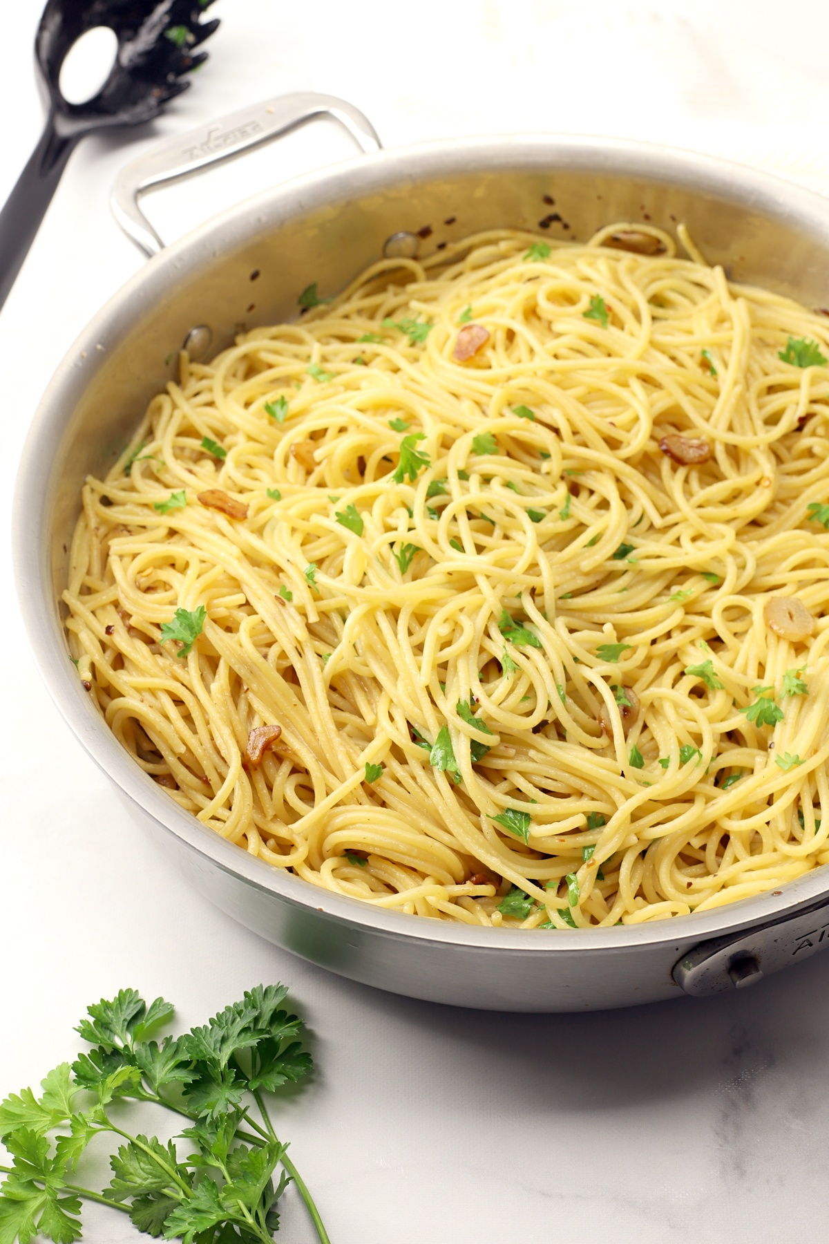 Spaghetti topped with sauteed garlic and chopped parsley.