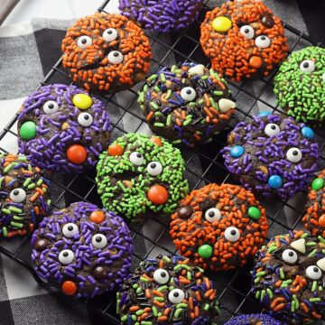Cooling rack filled with decorated Halloween cookies.