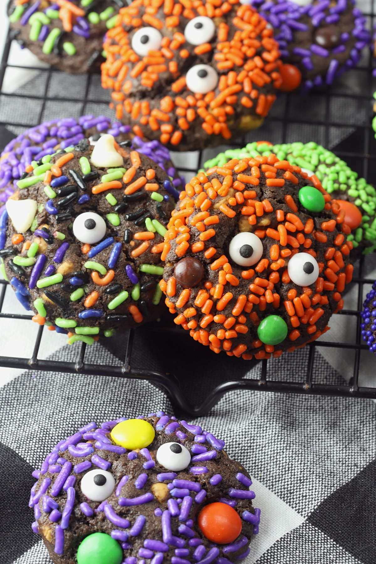 Chocolate cookies covered with sprinkles, candy eyeballs, and m&m candies.