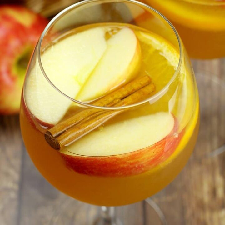 A wine glass filled with orange sangria with fruit and a cinnamon stick.