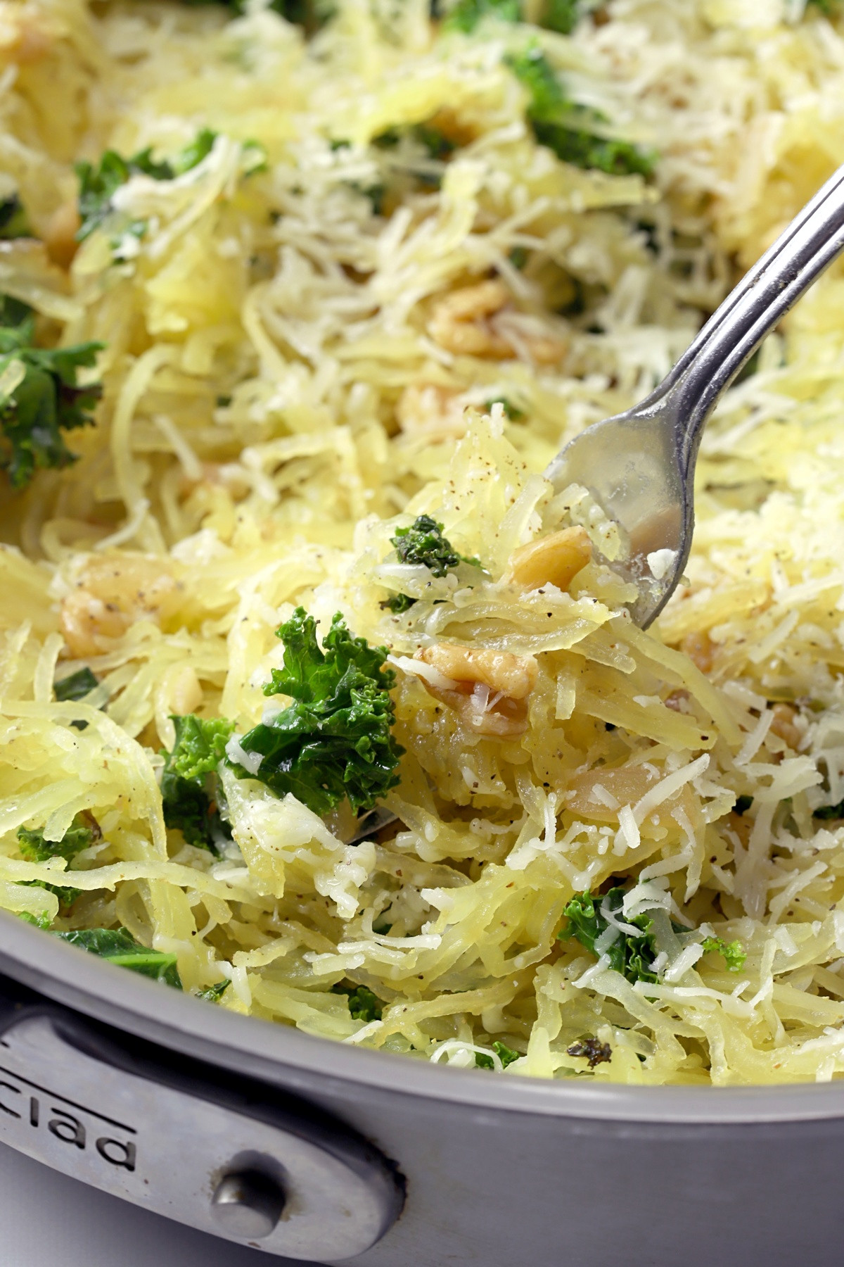 A fork picking up a bite of spaghetti squash and kale.