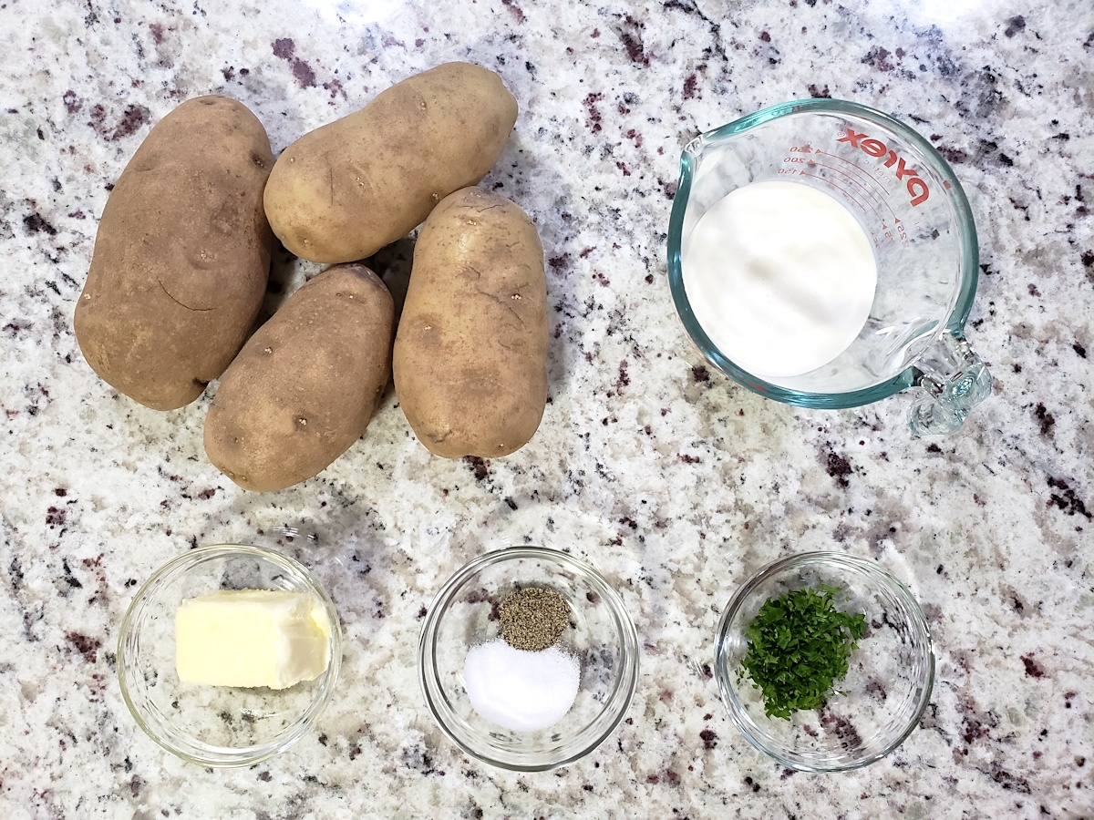 Potatoes and other ingredients on a counter top.