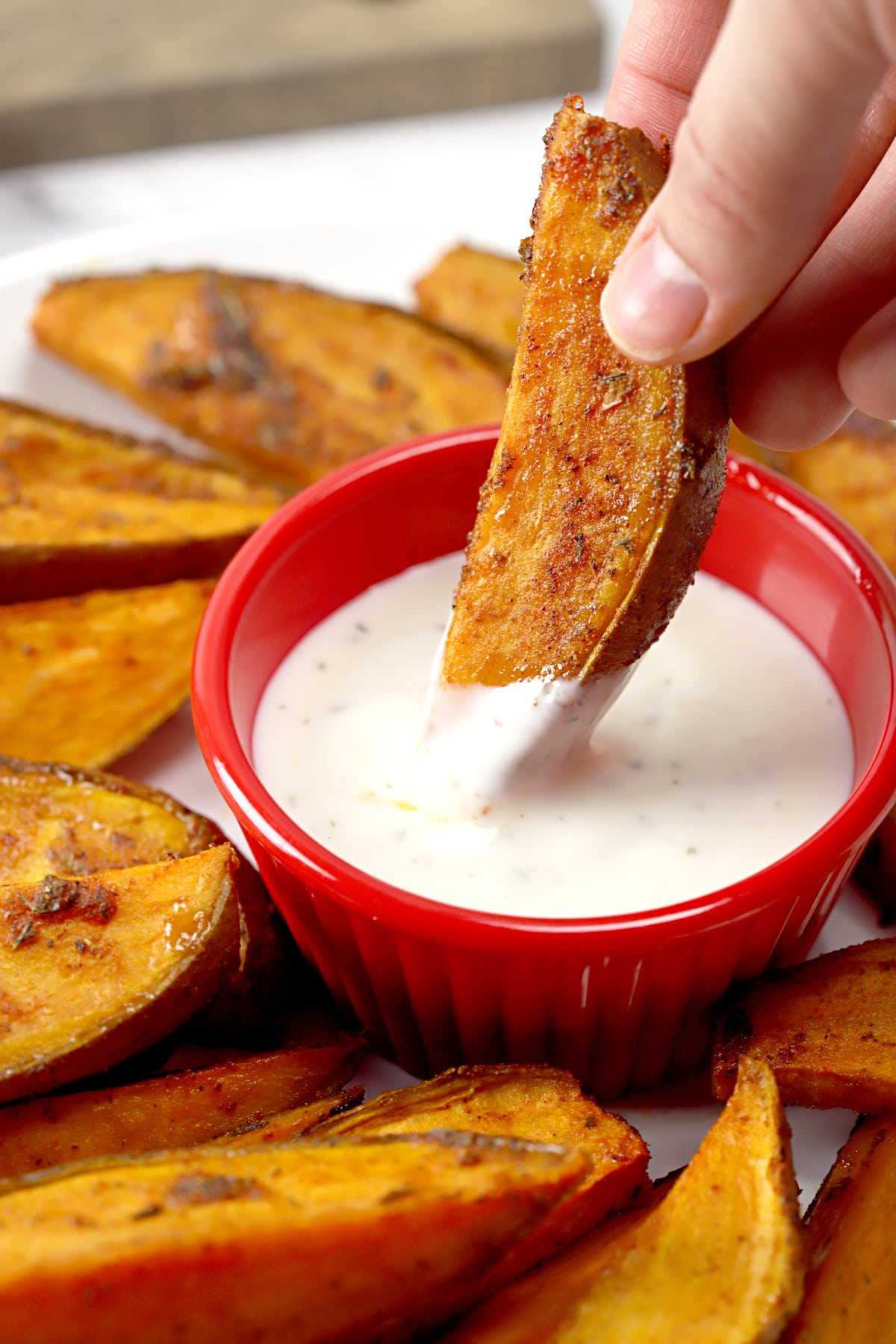 Dipping a sweet potato wedge into a bowl of ranch dressing.
