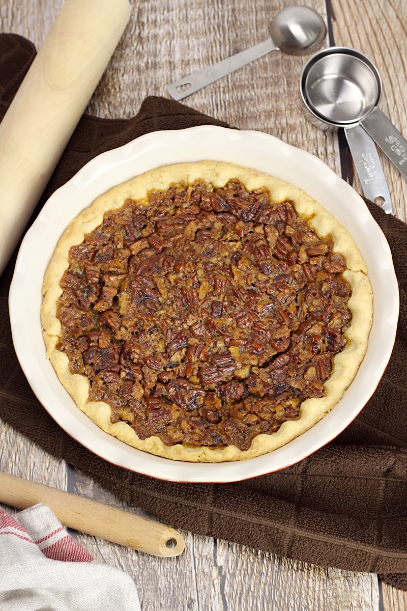 White pie pan filled with homemade pecan pie.