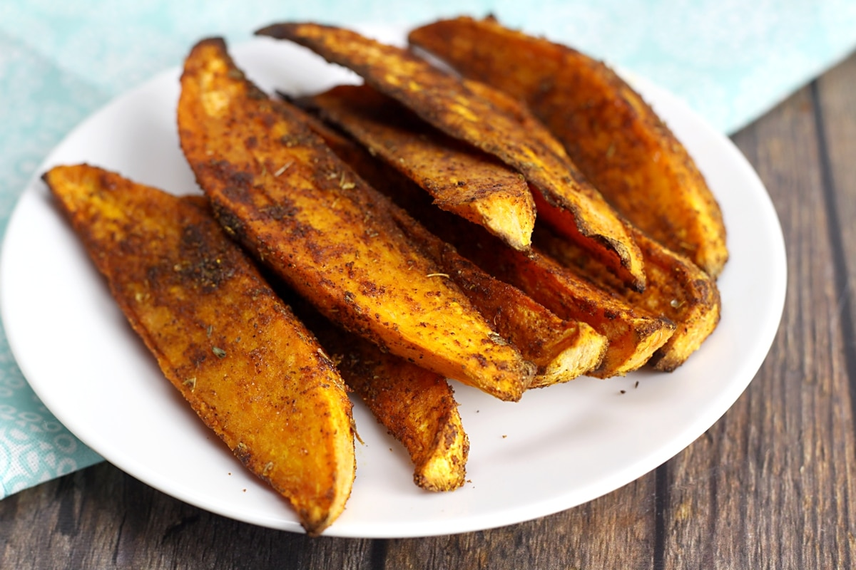 White plate filled with sweet potato wedges.