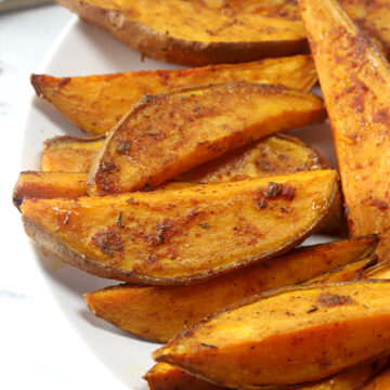 Sweet potato wedges on a white plate.