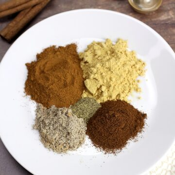 A round white plate with mounds of brown spices.