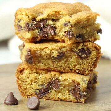 A stack of chocolate chip cookie bars on a cutting board.