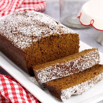 A serving plate of gingerbread with a red checked towel.