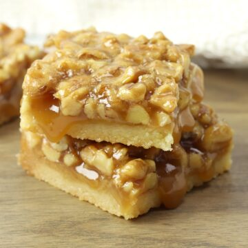 A stack of two shortbread bars topped with walnuts.