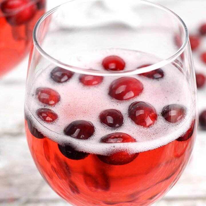 Fizzy prosecco added to a wine glass with cranberries.