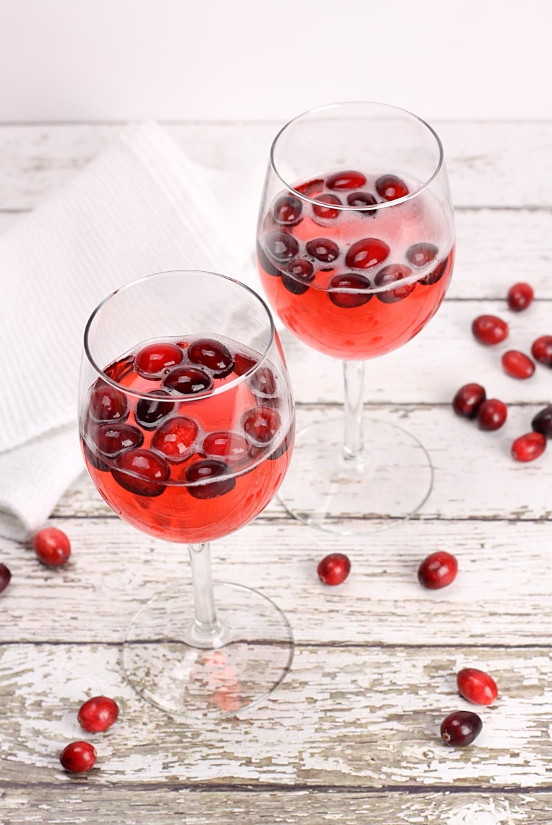 Two wine glasses filled with red wine and cranberries.