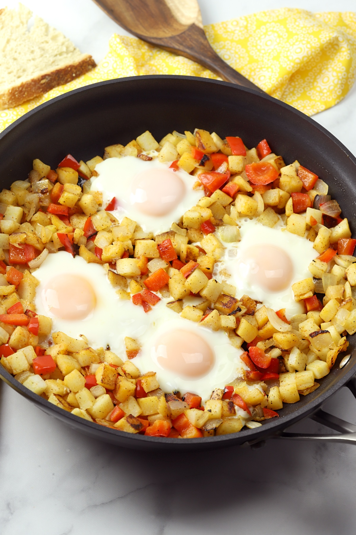 Sunny side up eggs nestled in a skillet of hash browns.