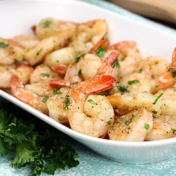 Shrimp coated in garlic butter and parsley, on a white serving plate.