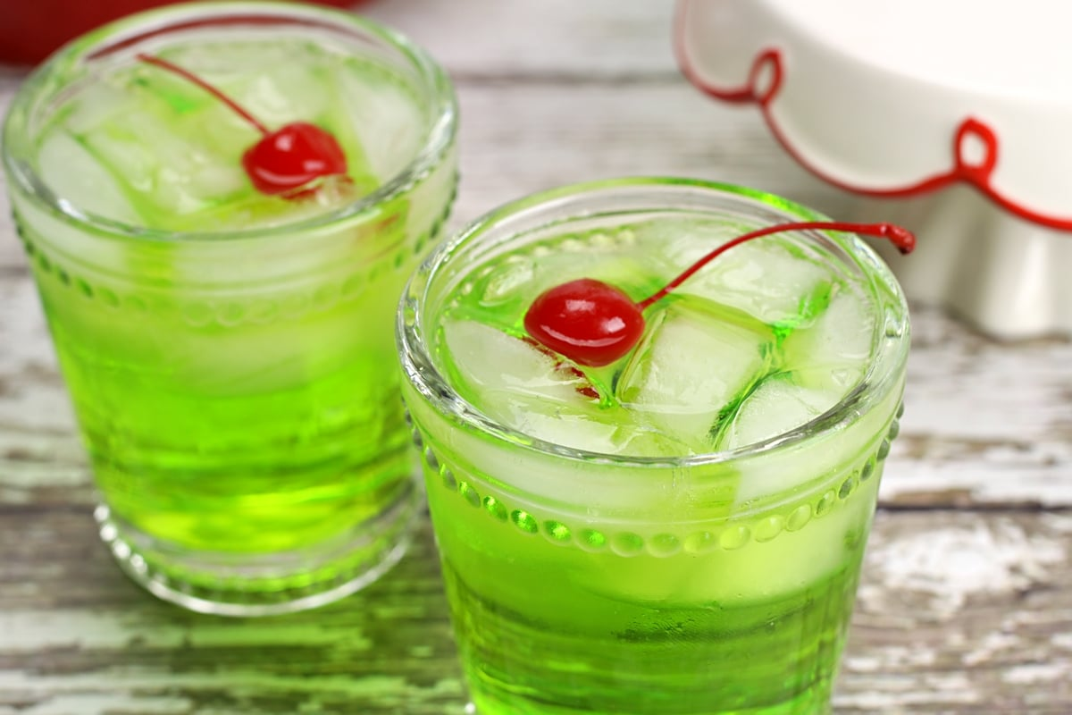 Two green cocktails in lowball glasses, with cherries on top.