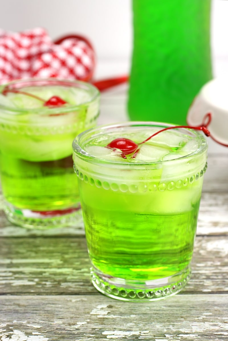 A glass filled with a green cocktail.