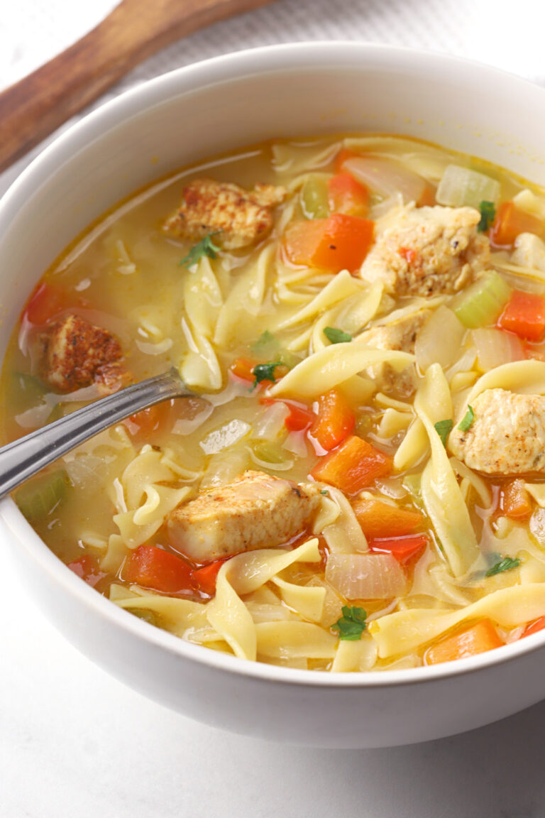 Chicken noodle soup in a bowl with a metal spoon.